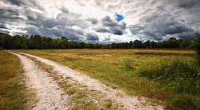 A quiet country road before a fall storm. stock photo