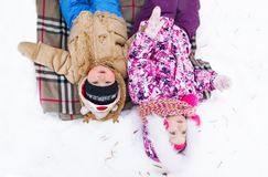 The quiet and cute kids lie on snow. Top view.  royalty free stock photography