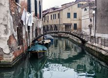 Quiet empty street in venice on a winter morning with a bridge crossing the canal and ancient buildings reflected in the water. A quiet empty street in venice on stock photo