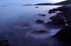 Quiet evening. Waves on the rocks stock image
