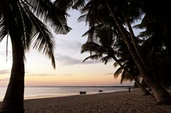 The peaceful evening on a beach. Madagascar. Quiet evening on a beach with the sea, palm trees and small boats. Madagascar royalty free stock images