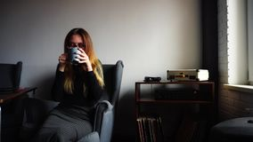 Quiet evening after cup of cocoa of beautiful girl who sits in gray armchair in stylish cafe in winter. stock footage