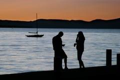 Quiet Evening at Lake. Man, woman and small sailboat at lake with beautiful sunset Stock Photo