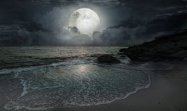 A quiet evening by the ocean. With moonlight and a big moon Royalty Free Stock Photo