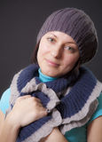Quiet happiness. Portrait to the young woman in a cap with a scarf on a black background Stock Photo