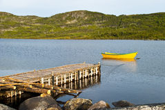 Quiet Lake. Calm Lake showing Dock Constructed of Rough Logs, a Moored Yellow Dory, and Distant Tree Covered Hills Stock Photography