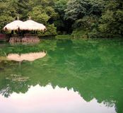 Quiet Lake. With a thatched straw roof pavilion Stock Photos