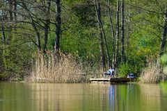 Quiet lake and fisherman Stock Image