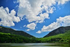 Quiet lake in the green mountains. On a background of blue sky with clouds stock images