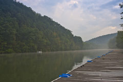 Quiet Lake Pier at Twilight. A tranquil scene on the dock by the lake near sunset Stock Photos