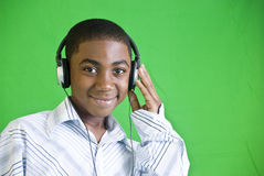 Quiet Listening. A young African American boy wearing headphones and smiling royalty free stock images