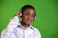 Quiet Listening. A young African American boy wearing headphones and smiling stock photography