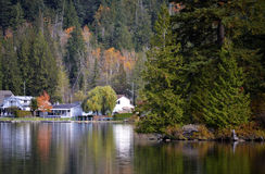 Quiet Living. A peaceful lake with cabins surrounded by trees Royalty Free Stock Photo