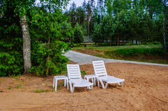 Quiet location on the sandy beach between the trees with two lounge chairs, you can escape and relax Stock Photo