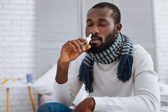Quiet man smelling nice nasal drops. Nasal drops. Cheerful calm young man smelling the scent of his new nasal drops while sitting with his eyes closed Stock Photos