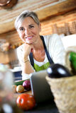 Quiet mature woman standing in kitchen Royalty Free Stock Photography