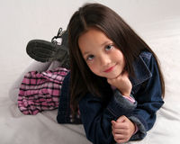 Quiet moment. Young girl in blue jean jacket and plaid skirt posing on floor Stock Photos