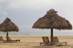 Quiet moments at the beach,on lounge chairs under tiki huts Stock Image