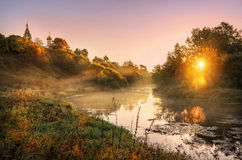 Quiet morning in the fog. Foggy golden morning on the river and the temple on the banks Stock Images
