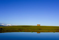 Reflection of wood hut, grassland and snow mountain at lakeside. Stock Photos