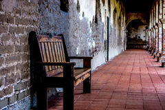 Quiet outdoor hallway at sunrise. Soft sunlight adds warmth to a rustic bench in an outdoor hallway at sunrise Stock Images