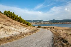 Country road towards the lake in Navarra, Spain. Quiet and peaceful landscape in Navarra. The road leads to the lake, around the fields and a calming landscape stock photography