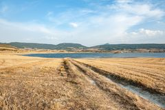 Country road towards the lake in Navarra, Spain. Quiet and peaceful landscape in Navarra. The road leads to the lake, around the fields and a calming landscape royalty free stock image