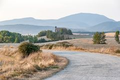 Country road near the church in Navarra, Spain. Quiet and peaceful landscape in Navarra. The road passes next to the ancient church and winds between the hills royalty free stock photo