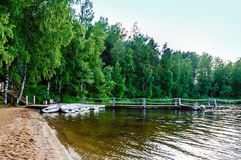 A quiet pier on the sandy shore of a forest lake with moored boats white. On a forest background stock images