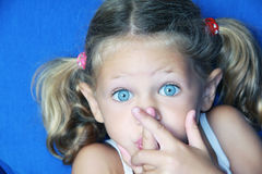 Quiet please. A young caucasian child with her hands to her mouth making a gesture to be quiet with a lovely expression on her face Royalty Free Stock Photo