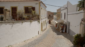 A quiet Portuguese alleyway with a local shop. A still shot of a quiet Portuguese alleyway with local souvenir shop fronts. Historically architectured european stock video footage