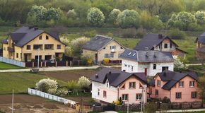 Quiet residential suburban area. Street with new modern comfortable brick cottages with yards and blooming gardens on background o. F beautiful green forest Royalty Free Stock Photography
