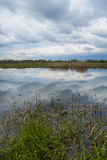Quiet river, clouds reflected in the calm water depths. Spring a Royalty Free Stock Image