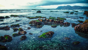 Quiet rock pool under a glowering sky. View of a quiet rock pool with clouds gathering over distant mountains Royalty Free Stock Photo