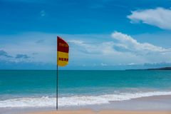 Quiet sand beach. have warning embroider flag on beach front of. It. have blue sea and clear sky are background. this image for nature,landscape,seascape and Stock Image
