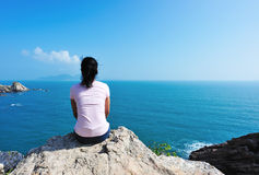 Quiet with the sea. Woman quiet sit face the sea under blue sky stock photography