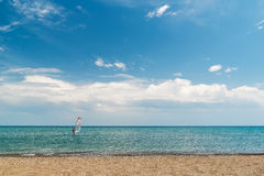 A quiet sea, blue sky, a surfer on the horizon, beach. A quiet sea, blue sky, a surfer on the horizon Royalty Free Stock Images