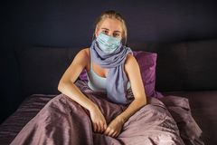 Quiet and serious infected young woman sits on bed and looks on camera. She is covered with blanket. Young woman has stock photo