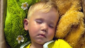Quiet sleep of a small child. Sleeping on pillows of bright colors royalty free stock image