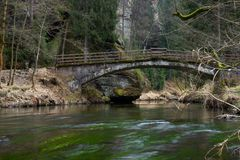 Quiet spring river in the forest with old bridge stock image
