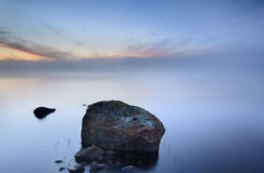 Quiet. Stone on a lake early misty morning Stock Photography