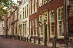 Quiet street with elegant semi-detached brick buildings and lamps at the end of the day in Delft. royalty free stock photos