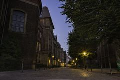 A quiet street with tall buildings at dusk lit by street lanterns in Dusseldorf, Germany. A quiet street with tall buildings at dusk lit by street lanterns in stock photo