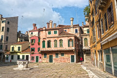 A quiet street in Venice. A beautiful quiet street in Venice, on a sunny summer day, old colorful houses with typical venetian windows, green wooden shutters and Stock Image
