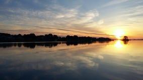 Quiet sunrise over the ocean. Dawn water reflection blue orange Stock Photos