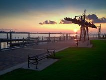 A quiet sunset on a desert pier with grass. A quiet sunset on a desert pier in usa with clouds , green and urban architecture royalty free stock image