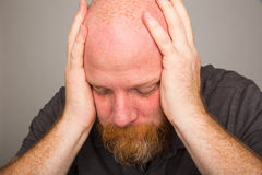Quiet time for a man. A bald man with a beard holding his hands over his ears Stock Photo