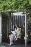 Quiet Time with Mom. A mother and her two-year old son enjoy reading a book together while sitting on a swing in an arbor. Room around image for text Royalty Free Stock Photography