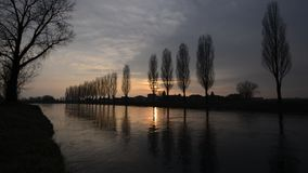 Quiet water flow of an irrigaion canal at sunset in the countryside stock video footage