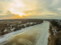 A quiet winter evening by the river. Sunset. The river Mologa in the winter evening. At the village Stock Images